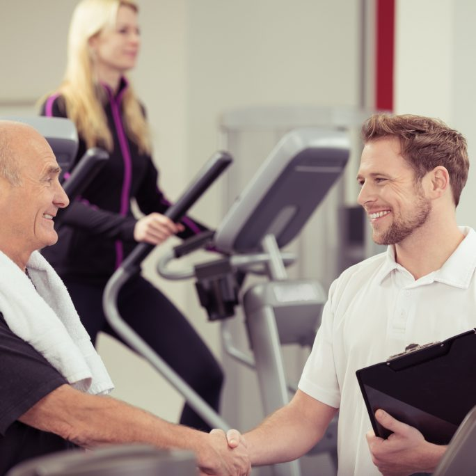 Close up Happy Old Man Shaking Hands with his Young Male Instructor at the Fitness Gym